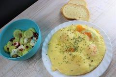 stekte ägg med smältt ost på den vita plattan med grönsaksalladen på sidan royaltyfria bilder