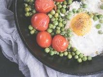 Stekte ägg med tomater och gröna ärtor arkivbild