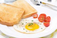 Stekte ägg, nya tomater och frasigt rostat bröd för frukost Arkivbilder