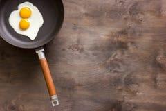 Stekte ägg på en brun träbakgrund fotografering för bildbyråer