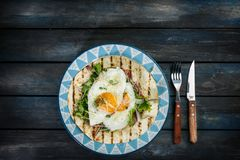 Stekte ägg på mjöltortillan med grön sallad och ost Användbar frukost- eller lunchidé Gaffelkniv och härlig maträtt royaltyfria bilder