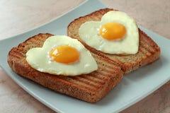 Stekte ägg som en hjärta på en rostat bröd Fotografering för Bildbyråer