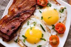Stekte ägg stekte bacon och körsbärsröda tomater som strilades med persilja Royaltyfria Bilder