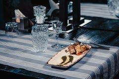 Stekte aubergine som är välfyllda med tomaten och ost på en vit platta med sås På en blå bordduk som göras randig med kniven och Royaltyfri Fotografi