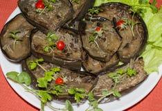 Stekte aubergineskivor med vitlök och körsbärsröda tomater Arkivfoton
