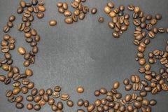 Stekte bruna kaffebönor på ett mörker - grå bakgrund Arkivbilder