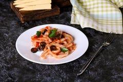 Stekte cirklar av tioarmade bläckfisken med örter, tomater och oliv Royaltyfri Foto