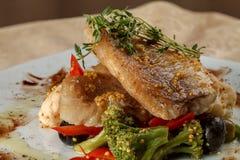Stekte filéer av den vita fisken på grönsaker royaltyfri bild
