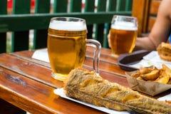 Stekte fisk och potatisar på den disponibla pappers- plattan och kylt exponeringsglas av utkastöl på trätabellen i utomhus- kafé fotografering för bildbyråer