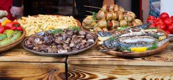 Stekte fisk, potatisar, champinjoner och grönsaker Arkivfoton