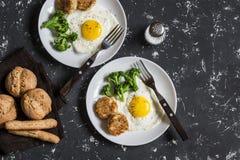 Stekte ägg, broccoli, fega köttbullar, hemlagat bröd för helt vete - smaklig enkel matställe På en mörk bakgrund Royaltyfria Foton