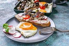 Stekte ?gg, sm?rg?s med ost, champinjoner, r?disor och gr?splaner frukost arkivbilder