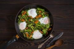 Stekte grönsaker och ägg i en stekpanna på en mörk trätabell royaltyfria bilder
