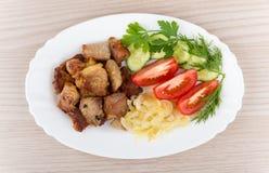 Stekte griskött och lökar med tomater, gurkor i maträtt Royaltyfri Fotografi