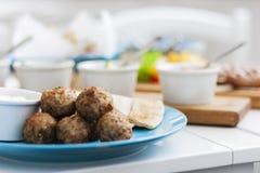 Stekte köttbollar med mintkaramellen och äpplet med vit sås och plana kakor - traditionell grekisk lunch på en blå platta i en re arkivfoto