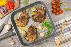 Stekte köttskivor i pannan, peppar för vitlök för tomatgräsplanlökar, smaklig mat Baktala gaffeln, på trätabellen, bakgrund Arkivfoto