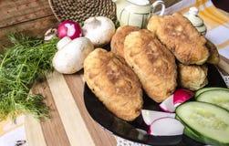 Stekte kakor med potatisar, champinjoner och en dill Arkivfoton