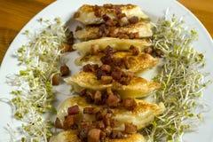 Stekte klimpar med ost och griskött som skrapar på trätabellen Royaltyfria Foton