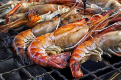 Stekte konungräkor som är havs- vid brand och BBQ-flammor Restauranggrillfest på nattmarknaden Royaltyfri Bild