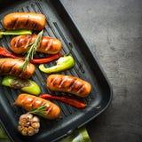 Stekte korvar med grönsaker i gallerpanna på svart bakgrund Royaltyfria Bilder
