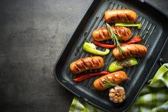 Stekte korvar med grönsaker i gallerpanna på svart bakgrund Arkivbilder