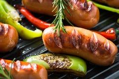 Stekte korvar med grönsaker i gallerpanna på svart bakgrund Arkivfoto