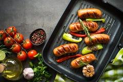 Stekte korvar med grönsaker i gallerpanna på svart bakgrund Fotografering för Bildbyråer