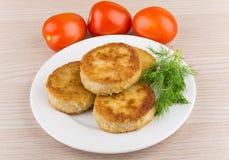 Stekte kotletter i platta med dill och tomater på tabellen Royaltyfri Bild