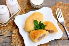 Stekte kryddiga kött- och potatissmå pastejer på en vit platta Potatissmå pastejer som är välfyllda med jordnötköttreceptet Lantl royaltyfria bilder