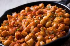 Stekte kryddiga kikärtar i stekpanna på trätabellen Royaltyfri Foto
