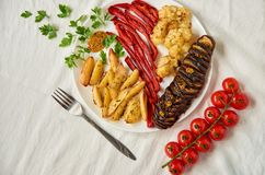 Stekte potatisar, aubergine, spansk peppar och blomkål på den vita plattan som dekoreras med gaffeln, nya körsbärsröda tomater oc Royaltyfri Foto