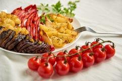 Stekte potatisar, aubergine, spansk peppar och blomkål på den vita plattan som dekoreras med gaffeln, nya körsbärsröda tomater oc Arkivbild