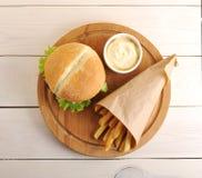 Stekte potatisar i en pappers- påse, en ostsås och en hamburgare Fotografering för Bildbyråer