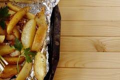 Stekte potatisar i folie från ugnen royaltyfria foton