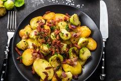 Stekte potatisar med Bryssel groddar och bacon Arkivfoton