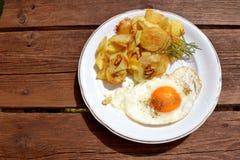 Stekte potatisar med det stekte ägget och rosmarin Arkivfoton