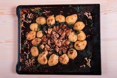 Stekte potatisar med höna och champinjoner på rosa bakgrund Arkivbilder