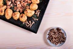 Stekte potatisar med höna och champinjoner på rosa bakgrund Royaltyfria Bilder