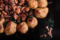 Stekte potatisar med höna och champinjoner på svart bakgrund Arkivbilder