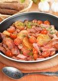 Stekte potatisar med meat och grönsaker Arkivbild