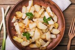 Stekte potatisar med persilja och löken i en lergodsmaträtt Arkivbilder