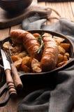 Stekte potatisar och grillade korvar i panna med gaffeln, kniven, den gråa servetten och skärbrädan arkivfoto