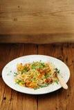 Stekte potatisar på den vita plattan med gaffeln Arkivbilder