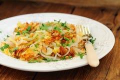 Stekte potatisar på den vita plattan med gaffeln Royaltyfri Foto
