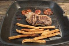 Stekte potatisar, stekte tomater och ett stycke av kött Arkivbilder
