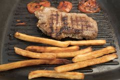 Stekte potatisar, stekte tomater och ett stycke av kött Arkivfoto