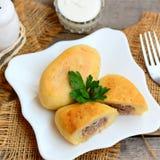 Stekte potatiskotletter som är välfyllda med kött på en vit platta och på en gammal träbakgrund Hur man gör färs välfyllda potati royaltyfria bilder