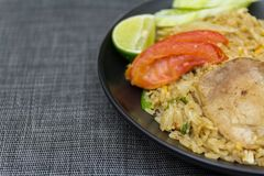 Stekte ris med griskött, limefrukt, potatisen och gurkor i svart platta Fotografering för Bildbyråer
