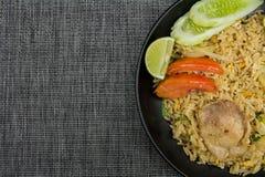 Stekte ris med griskött, limefrukt, potatisen och gurkor i svart platta Arkivfoto
