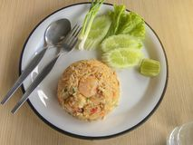 Stekte ris med räka i thailändskt dekorerar maträtten med salladslöken, gurkan, grönsallat, chili och citronen royaltyfri foto